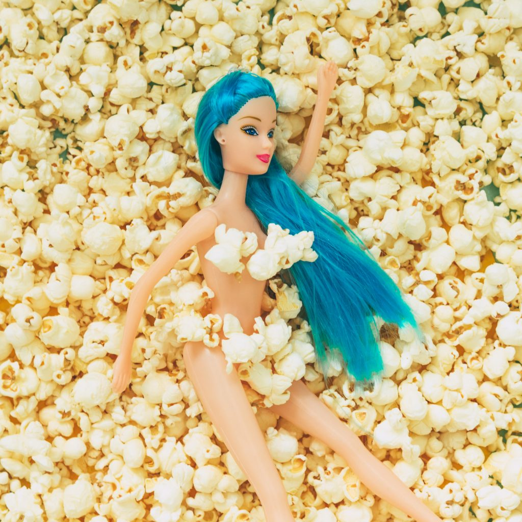 Blue haired girl doll laying on a bed of popcorn.